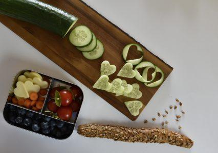 Lunchbox gefüllt mit Obst, Gemüse und Käse.