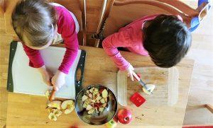 Kinder helfen beim Äpfel schneiden