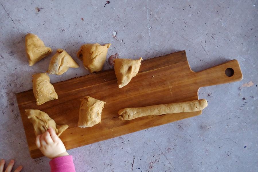 Kinderhand greift Teig mit Vollkornmehl an